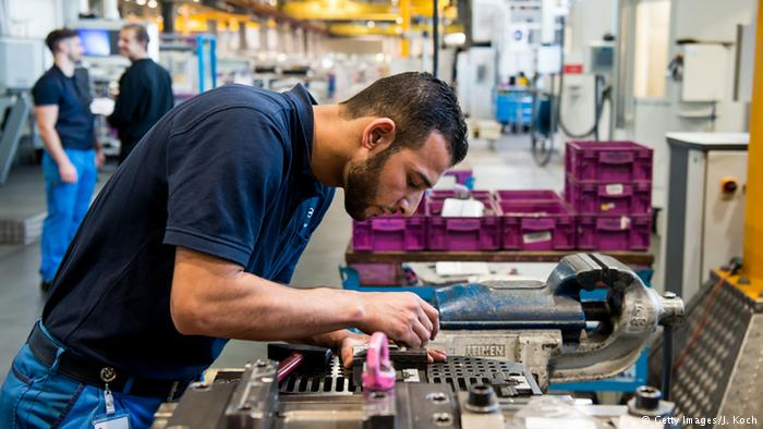 Image Credit: Deutsche Welle - Syrian Refugee Working at BMW